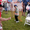 Cherry Festival Ambassador (volunteer) Vern Barker assists Jacob Harrand, 4, from Traverse City, Mich., at the fish pond during the 78th Annual National Cherry Festival Monday, July 04, 2004 in Traverse City, Mich.  Barker was trying to have Harrand hold his fish he caught.<br /> <br /> <br /> <br /> (AP Photo/Traverse City Record-Eagle, Douglas Tesner)