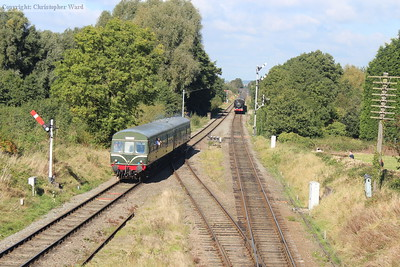 The DMU pulls away and prepares to pass the approaching Pannier tank