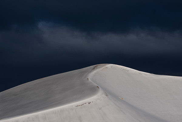 A recent snowstorm blankets the dunes in white while another storm waits in the distance.   Great Sand Dunes National Park.