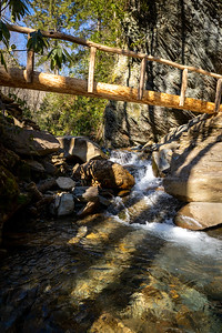log bridge over a small waterfall along a cliffside in the great smoky mountain national park