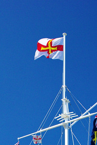 Harbor Mast to honor the liberation of Guernsey Island from the Nazis, WW2.  The Guernsey Island flag is at the top.