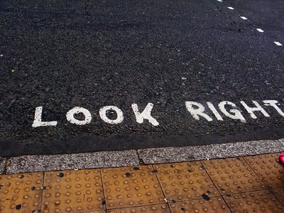 """Warning signs to non-British pedestrians to """"LOOK RIGHT"""" before crossing the street.  The people in England drive on the wrong side of the road."""