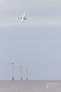 Catalina flying boat amphibious aircraft flying over offshore windfarm turbines