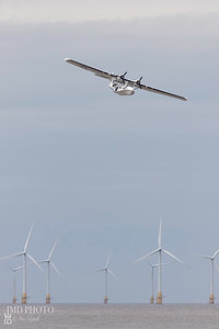 Catalina flying boat amphibious aircraft flying over offshore windfarm turbines at the Great Yarmouth