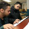 Greater Lowell Boys and Girls Club youth of the year Jeremy Encarnacion gets some help learning how to play chopsticks from youth leader Nicholas Figueroa, on left, at the club on Friday afternoon. SUN/JOHN LOVE