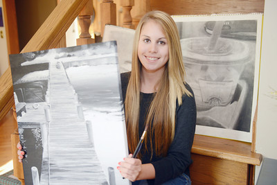 Young American Jenna Aumiller, a Midd West student, holds a painting of hers at her home in Beaver Springs.