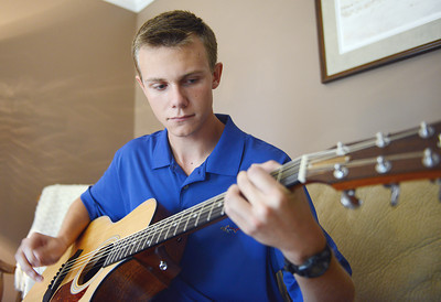 Young American Alex Mettler, of Danville, plays guitar in his home.