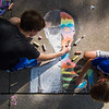 Gabe Stumbris, 16 of Lewisburg, and his brother Simon Stumbris, 13 of Lewisburg, work on their half-man half-rainbow-skelton piece during the Lewisburg Sidewalk Chalk Festival on Friday.