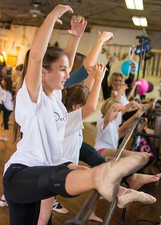 Gianna Feldmann, 11 of Danville, smiles while stretching on the ballet bar during Athen-Thon, a dance marathon to raise money for Athena Zellers.