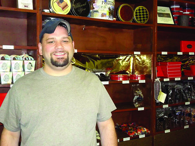 "William Lang of Lang's Chocolates makes his candy, including the Gourmet Chocolate ""Salami"" hanging on a shelf to the right, in his Pine Street shop."