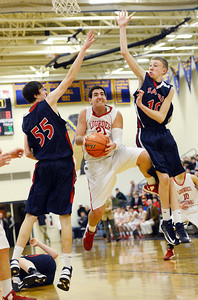 Our Lady of Lourdes' Anthony Pennypacker jumps between Sayre's Joey Galizia and Marshall Highley during the PIAA District 4 Boys Class A Basketball playoff game in Montoursville on February 21, 2013.