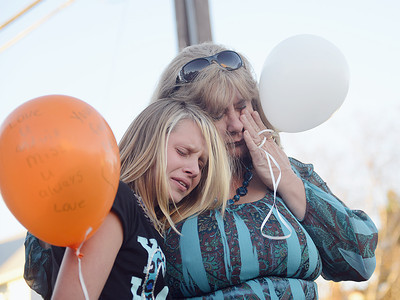 Lisa Weikel, of Selinsgrove, wipes away tears while comforting Alexis Clinger, 13, during a memorial balloon release for Weikel's son Robert Hill on Tuesday evening. Hill was killed in an automobile accident on September 17, 2012.