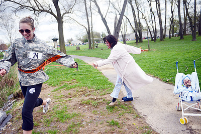 Alison Tomko, of Selinsgrove, grabs strip of the belt of a runner during the Zombie Run at the Selinsgrove Kidsgrove on Saturday morning. The goal of the 5K was to get through all the zombies on the course and have at least one strip remaining on your belt.