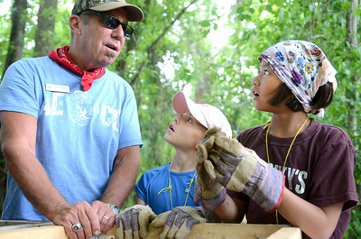 Bruce Baker, left, of the Ned Smith Center, talks with Isabella DiSanto, 8, Harrisburg, and Emily Snyder, 10, Dauphin County, as he helps them sift through dirt at the Fort Halifax site on Wednesday morning during Archeology camp.