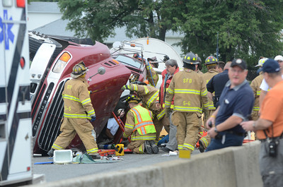 Fire figthers try to extract the driver of a 18 wheeler from his cab after it rolled on its side Wednesday morning in Sunbury on the on ramp of the Veterans Memorial Bridge.