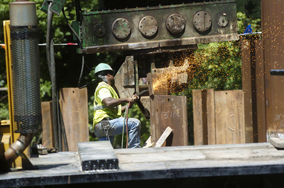 A Susquehanna Valley Construction Corp. employee uses a cutting torch on a section of metal sheeting at the site of the iron bridge in Paxtonville on Monday as construction of a new bridge continues.