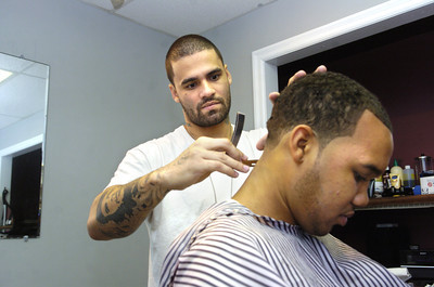 Frank Rodriquez uses a straight razor to finish up a hair cut on Jesse Garcia of Milton at the new Against The Grain barber shop in Milton.