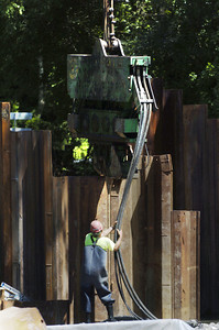 A Susquehanna Valley Construction Corp. worker moves an ice hammer into place to pound metal sheeting into the creek bed where the old iron bridge in Paxtonville was as construction on a new bridge continues.