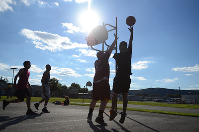 Ray Dalton, left, and Robert Easton, watch Jeffrey Heintzelman try and block the shot of Joshua Barley during a pickup game in Sunbury on Monday afternoon.