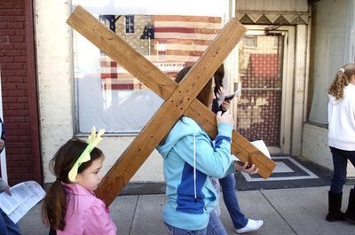 Amelia Benjamin, 6, left, Danville, and Alexa Willoughby, 12, Danville, help each other carry a cross during a crosswalk through Danville on Friday.