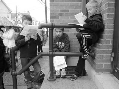 Nicholas Willoughby, 7, left, recites a prayer along side Luke Hilkert, 9, and Luke Huron, 9, at the start of Friday's cross walk in Danville.