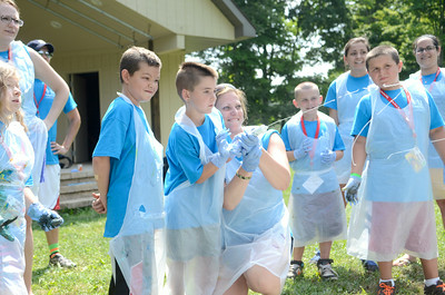 Campers and counselors at Camp Dost spray paint out of syringes during an art project on Tuesday at the camp.