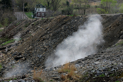FILE - In this May 2, 2007 file photo, steam from burning underground coal rises from the ground in  Centralia, Pa. Fifty years ago on Sunday, May 27, 2012, a fire at the town dump spread to a network of coal mines underneath hundreds of homes and business in the northeastern Pennsylvania borough of Centralia, eventually forcing the demolition of nearly every building. (AP Photo/Carolyn Kaster, File)