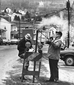 FILE - In this April 1981 file photo, U.S. Bureau of Mines' John Stockalis, right, and Dan Lewis drop a thermometer through a hole on Main Street in Centralia, Pa., to measure the heat from a shaft mine blaze that burns under the town. Fifty years ago on Sunday, May 27, 2012, a fire at the town dump spread to a network of coal mines underneath hundreds of homes and business in the northeastern Pennsylvania borough of Centralia, eventually forcing the demolition of nearly every building. (AP Photo/Paul Vathis, File)