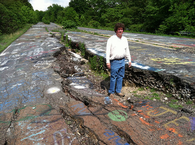 In this May 24, 2012 photo, David DeKok poses on abandoned Route 61 in Centralia, Pa. Fifty years ago on Sunday, May 27, 2012, a fire at the town dump spread to a network of coal mines underneath hundreds of homes and business in the northeastern Pennsylvania borough of Centralia, eventually forcing the demolition of nearly every building.  (AP Photo/Michael Rubinkam)