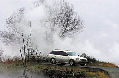 FILE - In this April 3, 2004 file photo, a motorist drives among the smoldering remains of land near Route 61 in Centralia, Pa. Fifty years ago on Sunday, May 27, 2012, a fire at the town dump spread to a network of coal mines underneath hundreds of homes and business in the northeastern Pennsylvania borough of Centralia, eventually forcing the demolition of nearly every building. (AP Photo/Republican & Herald, Johnathan Paroby, File)