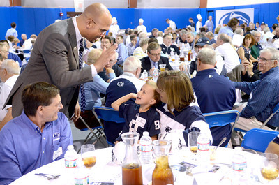 Penn State head football coach James Franklin goes to give a high five Jay Houseknecht, 5, and his grandmother Carol Houseknecht, Montoursville, at a Coache's Caravan event at Penn College in Williamsport on Tuesday.