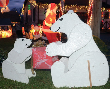A pair of wooden polar bears, made by Robert Snyder, sit outside their home in Milton.