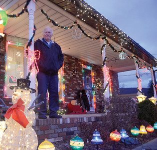 Robert Snyder stands on the porch of his home in Milton. Robert and his wife Doreen have been decorating their home for over 20 years, but this yeat will be their last.