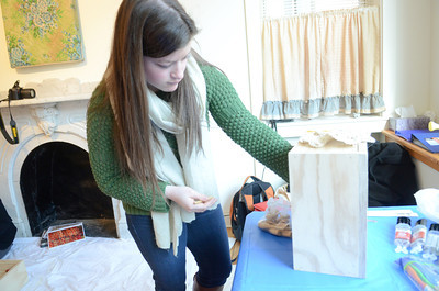 Bucknell University student Morgan Slade puts some of her found objects from a junk walk in a box that will house her art piece in connection with Bucknell's downtown art gallery on Monday.