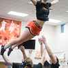 Taylor Kipp, 17, of Milton, falls in the arms of her teammates during a stunt at practice on Wednesday.