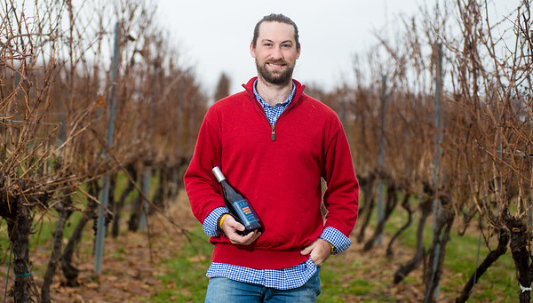 Nickolas Kifolo, head of marketing and distribution at Fero Vineyards and Winery, stands in their vineyard while holding a bottle of their award winning pinot noir wine, Bison Roots Blue.