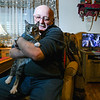 XXXX holds his cat Chester inside the living room of his Shamokin home. The security system sits in the background.
