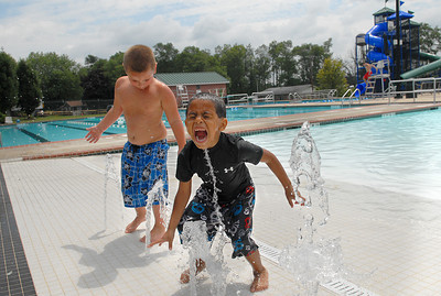 Brothers, Michael, 4, left, and Izayah Brownsberger, 4, both of Watsontown try to catch water while they have the Lewisburg Community Pool to themselves Friday July 27, 2012.