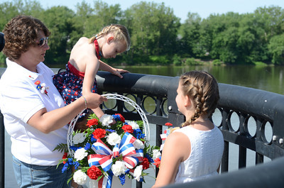Marleigh Davis, 6, second from left, Danville, gets a helping boost from Mary Mensch, Danville, while throwing flowers into the Susquehanna River with Reilly Mensch, 10, on Monday morning for a ceremony before the start of Danville's Memorial Day Parade.