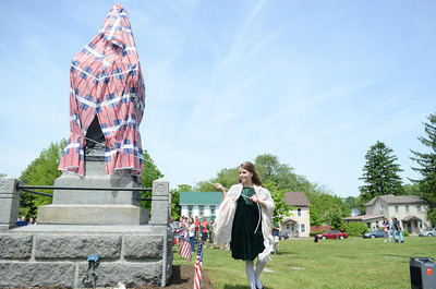 Natalie Imhoof, 10, Selinsgrove, takes off the cover over the statue of Gov. Simon Snyder in Selinsgrove during a re-dedication ceremony for it on Monday.