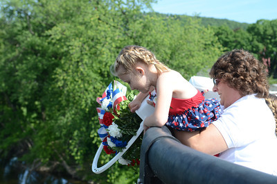 Marleigh Davis, 6, left, Danville, gets a helping boost from Mary Mensch, Danville, while throwing flowers into the Susquehanna River on Monday morning for a ceremony before the start of Danville's Memorial Day Parade.