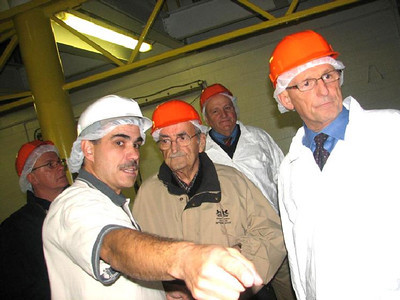 Frank Furman, vice president of quality for Furmano's, pointing, gives state Rep. Merle Phillips, center, and state Deputy Health Secretary Michael Huff, far right, a tour of the food company's plant in November, 2008.