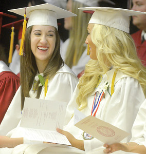 Hayley Daub and Carly Smith share a laugh at Millersburg Area High School's Commencement during Robert Deibler's speech on Wednesday.