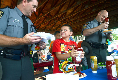 Logan Shaffer, 9, of Danville shares the ketchup with Sgt. Fredrick Dyroff, left, and Cpl. Craig Polen both with the State Patrol out of Milton during the National Night Out celebrations at Washies Park in Danville Tuesday night Aug. 7, 2012.