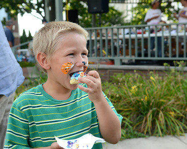 Dawson Finfinger, 7, of Sunbury devours the cookie he just decorated at the Children and Youth table Tuesday Aug. 7, 2012 during National Night Out in Cameron Park.