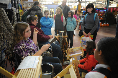 Karina Anderson, 11 of Palmyra, demonstrates drop spindling as her mother Ellen demonstrates spinning on a wheel during the PA Farm Show on Tuesday afternoon in Harrisburg.