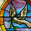 Dove holding a palm branch on a window at First Baptist Church.