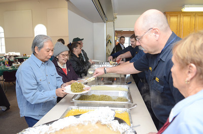 Giung Diep, left, of Lewisburg, gets a helping of green beans from Lewisburg Fire Department member Harold Erdley at the First Presbyterian Church in Lewisburg for their annual Thanksgiving dinner on Thursday.