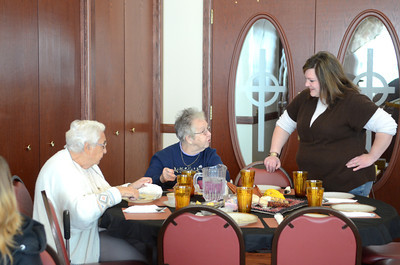 Diners Geri Schlegel, left, Selinsgrove, and Bea Swanger, Montandon, talk with volunteer Stephanie Hines, Selinsgrove, at the Thanksgiving dinner put on by the All Saints Episcopal Church on Thursday.