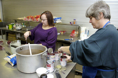 Kristen Bialecki, left, Danville, and Georgia Cole, Danville, help prepare for St. Joseph's in Danville annual Thanksgiving day dinner on Thursday.